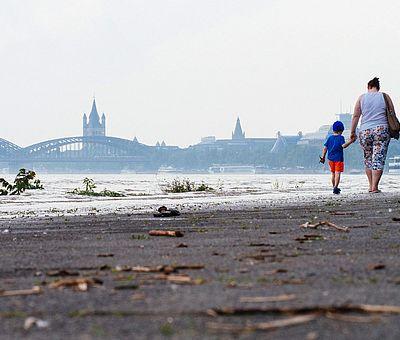 Spaziergang am Kölner Rheinufer bei Hochwasser. Im Hintergrund sind die Hohenzollernbrücke und die Romanische Kirche Groß St. Martin zu sehen. ©David Stoll