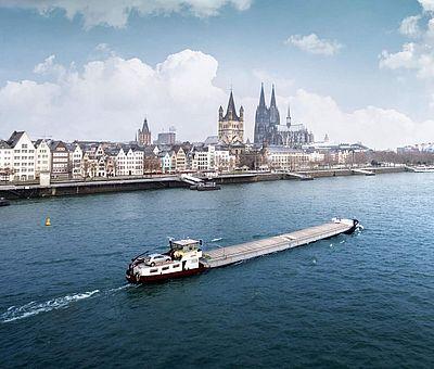 Schiff auf dem Rhein. Im Hintergrund sind die Kölner Altstadt, der Kölner Dom und die Hohenzollernbrücke zu sehen. ©mRGB/Shutterstock.com
